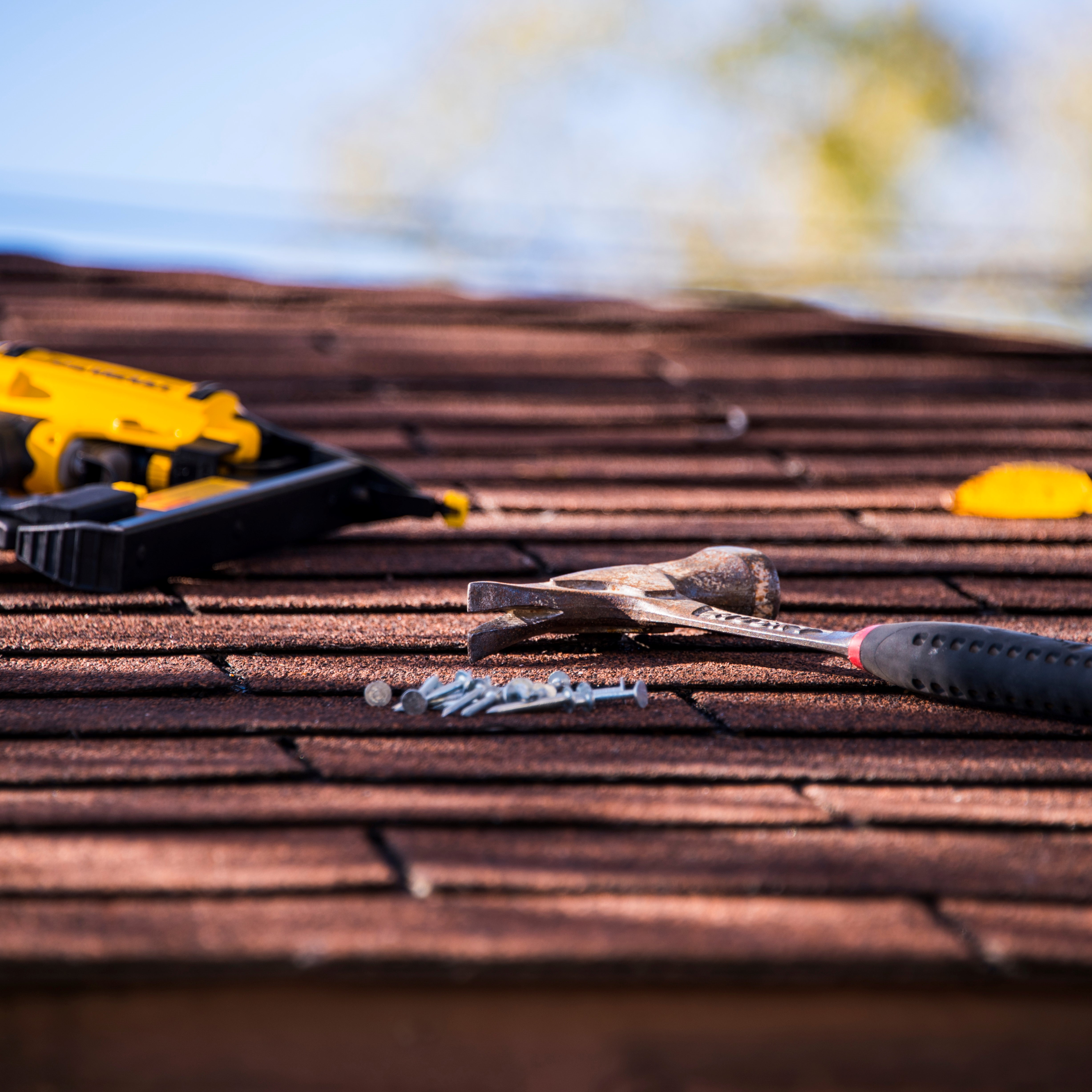 An asphalt roof with tools on it, including a hammer, nail gun, and nails.