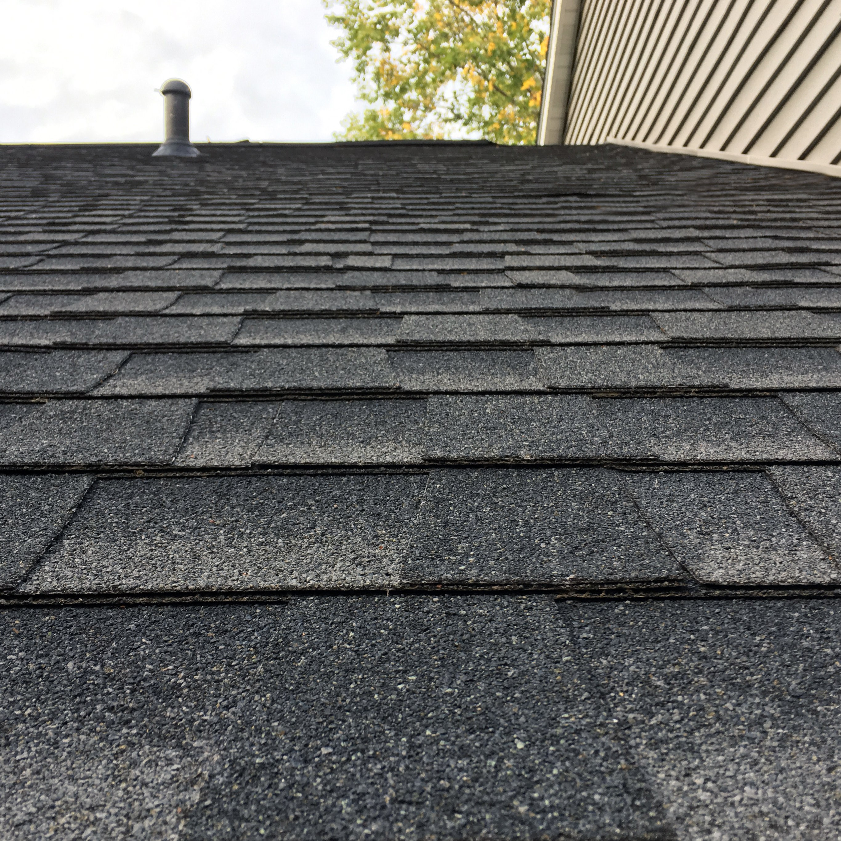 A section of perfect asphalt shingles on a rooftop.