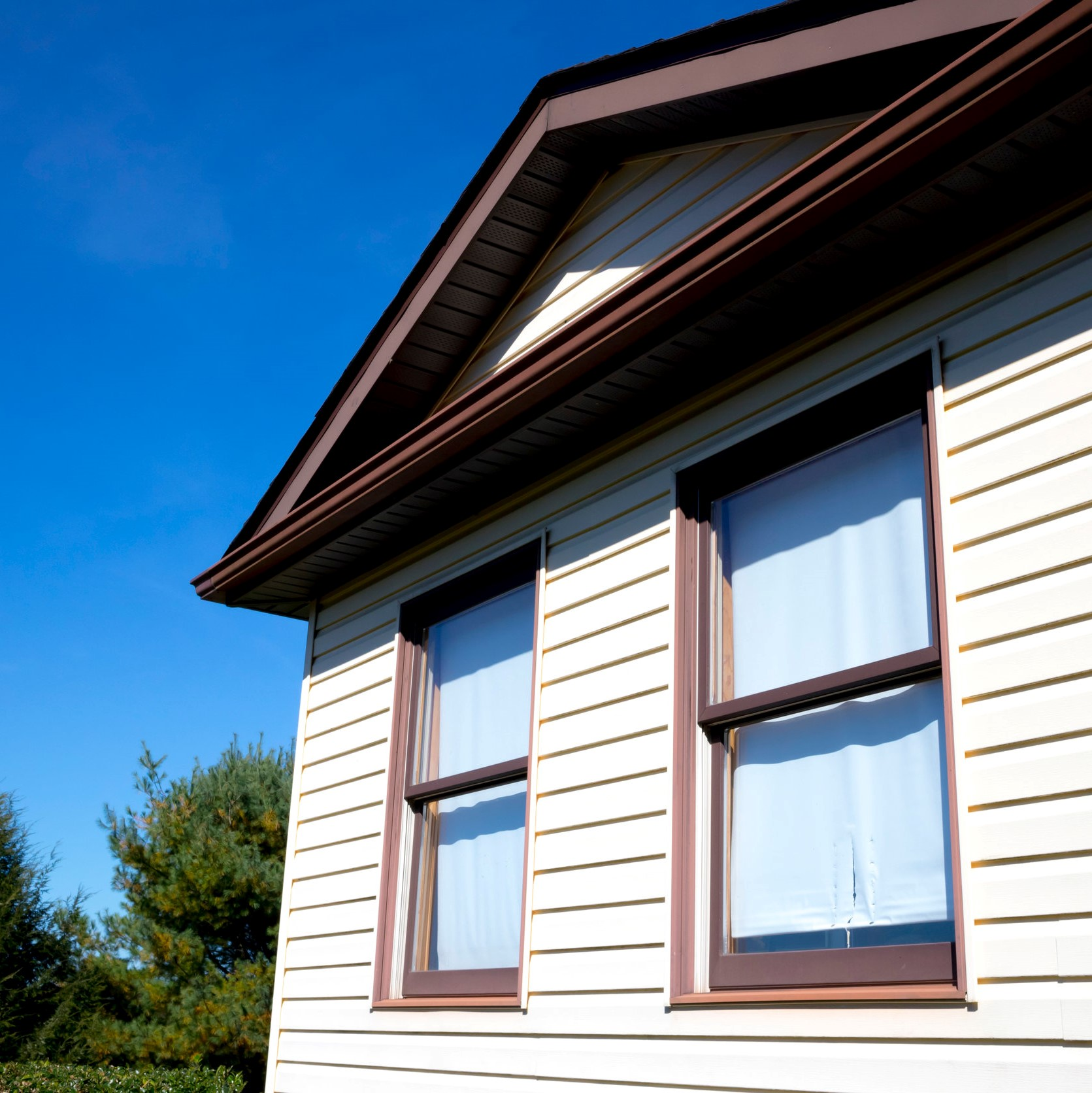 The side of a house with new off-white siding installed.