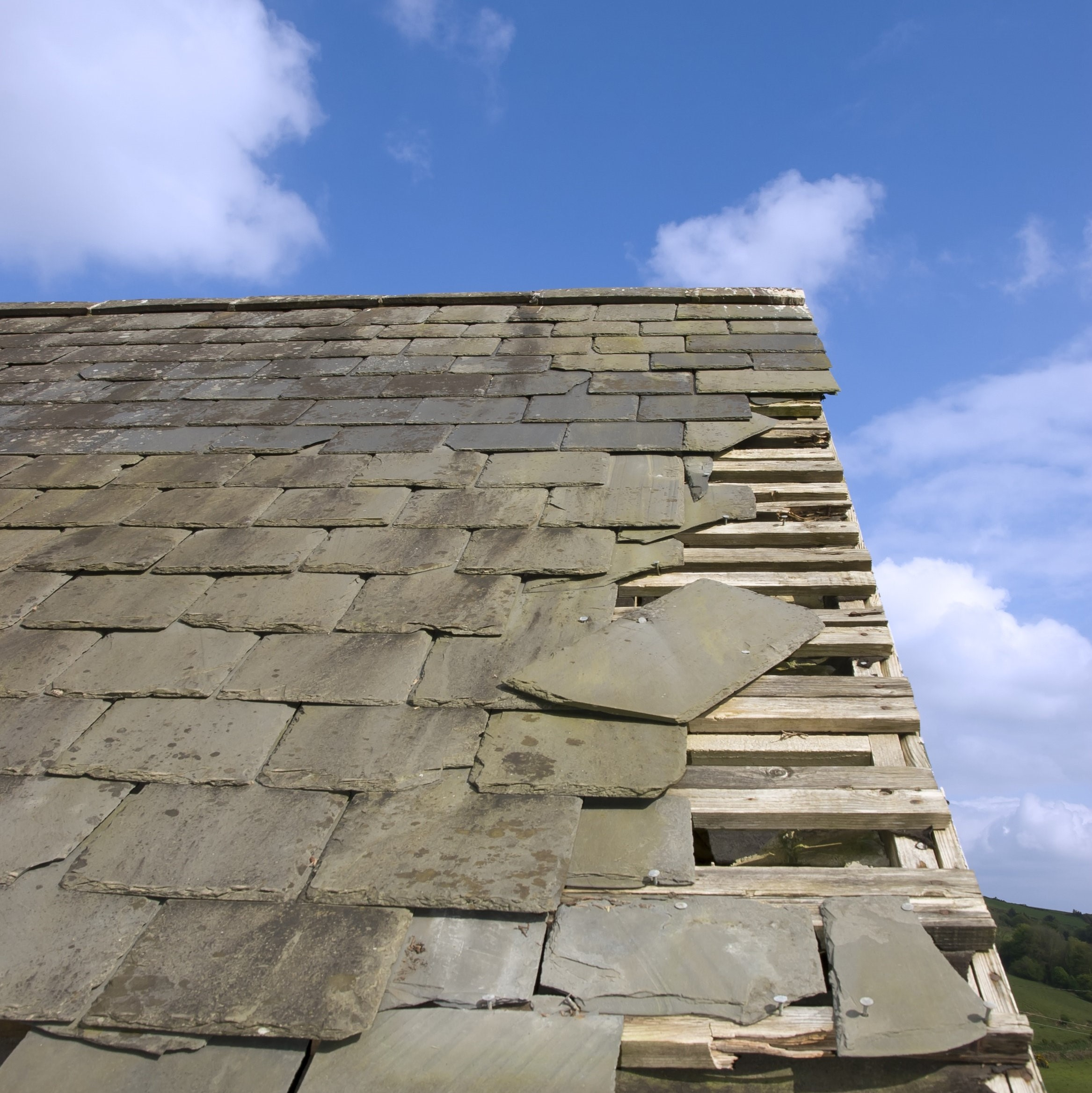 A roof in need of storm damage repair to its slate tiles.